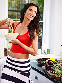 Padma Lakshmi holding bowl of pasta with pasta in her hand