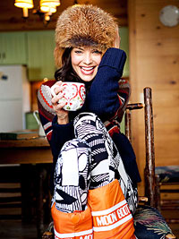 Woman smiling, bundled in warm clothing, holding coffee mug.