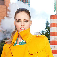 Woman in yellow coat, wearing lipstick, city background