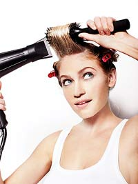 Woman using blowdryer, hair in curlers.