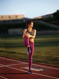 Woman on track, stretching leg