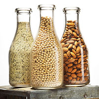 Three bottles filled  almonds, rice and soy beans
