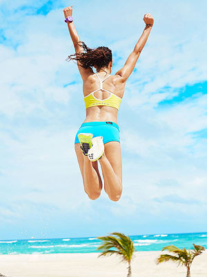 Woman jumping on beach in shorts and tank top