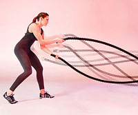 Woman working out with battle ropes, strength training