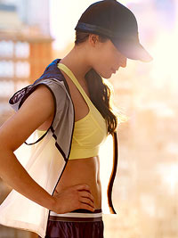Woman in workout gear, wearing a hat, sun protection, summer