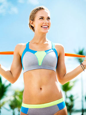 Woman in sporty swimsuit holding resistance band, stretching resistance band