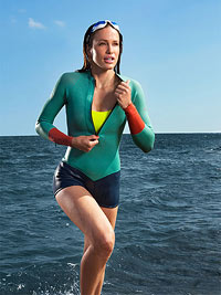 Woman in wetsuit, coming out of water.