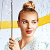Woman holding an umbrella in rain, topknot hairstyle