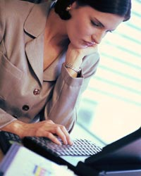 young woman frowning at desk at work