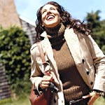 Woman looking up and smiling in brown turtle neck sweater and tan jacket
