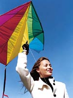 Happy woman flying Kite with Blue Sky