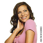 Woman with dark wavey hair in pink top smiling Constance Marie