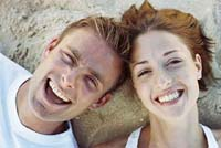 Man and woman lying on grass facing camera