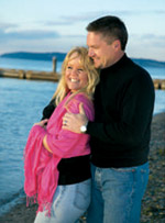 Husband In Black Holding Wife In Pink Wrap Standing By The Lake