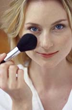 Blonde woman powdering face with brush