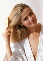 Young blonde woman brushing her hair