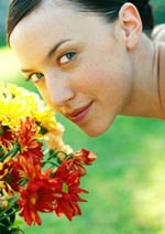 Young woman smelling flowers in garden