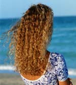 Back of woman with long curly hair at the beach