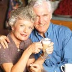 Elderly couple drinking coffee and smiling at camera