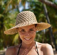 Young woman with straw hat on beach