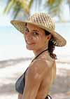 Woman in bikini on beach wearing straw hat