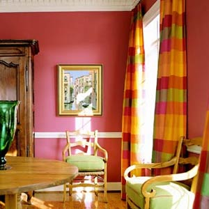 Red wall dining room with green chairs