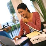 black haired woman smiling while on phone and using computer at desk