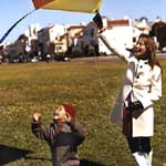 Woman In White coat flying kite with son
