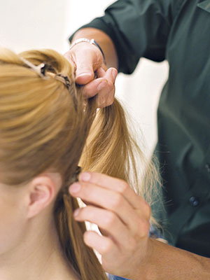 hairdresser grabbing woman?s hair in a ponytail