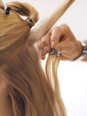 hairdresser putting in hair extensions