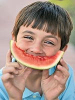 Boy smiling holding watermelon slice