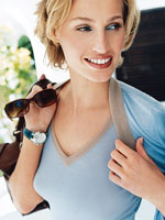blond woman in blue t-shirt holding sunglasses and bag