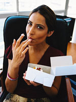 brunette woman holding open pastry box with cupcake licking frosting off fingers