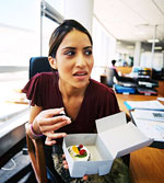 brunette woman secretively holding open box with frosted cupcake in it