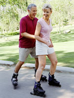 elderly man and woman rollerblading him supporting her from behind
