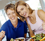 two women eating salads in kitchen smiling