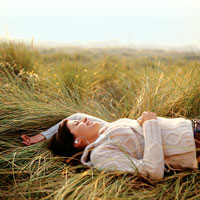 woman laying in field listening to music on ipod