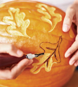 U-gouge tool carving leaf design into pumpkin