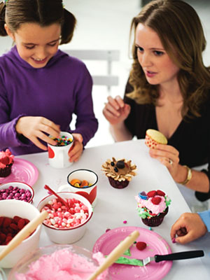Woman and child decorating cupcakes
