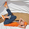 girl in orange shirt and hat and jeans lying on back