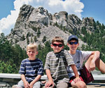 three boys in front of Mount Rushmore