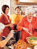 Paula deen tossing greens in bowl with man and woman behind her