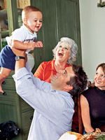 man lifting up baby, Paula deen smiling in background