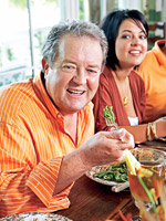 man eating greens with woman in background