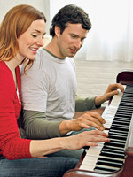 wife and husband playing piano