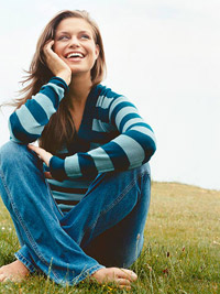 Model sitting in grass smiling