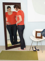 Woman feeling fat in mirror