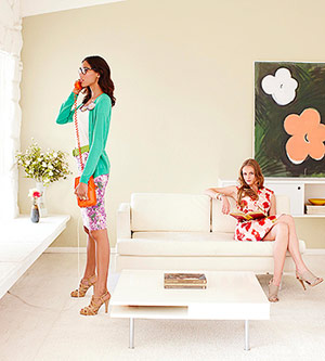 Two models wearing floral dresses in living room