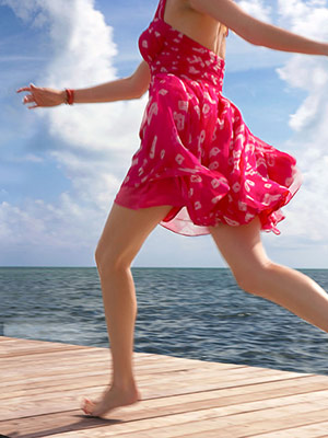 Model in hot pink sundress running