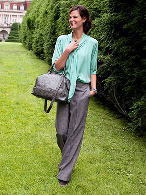 Model in green top and grey pants